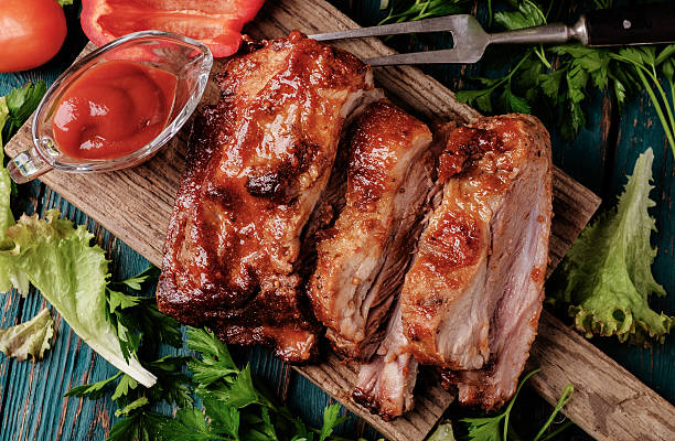 Delicious barbecued ribs seasoned with a spicy basting sauce Delicious barbecued ribs seasoned with a spicy basting sauce and served with chopped fresh vegetables on an old rustic wooden chopping board in a country kitchen. Top view. pork stock pictures, royalty-free photos & images