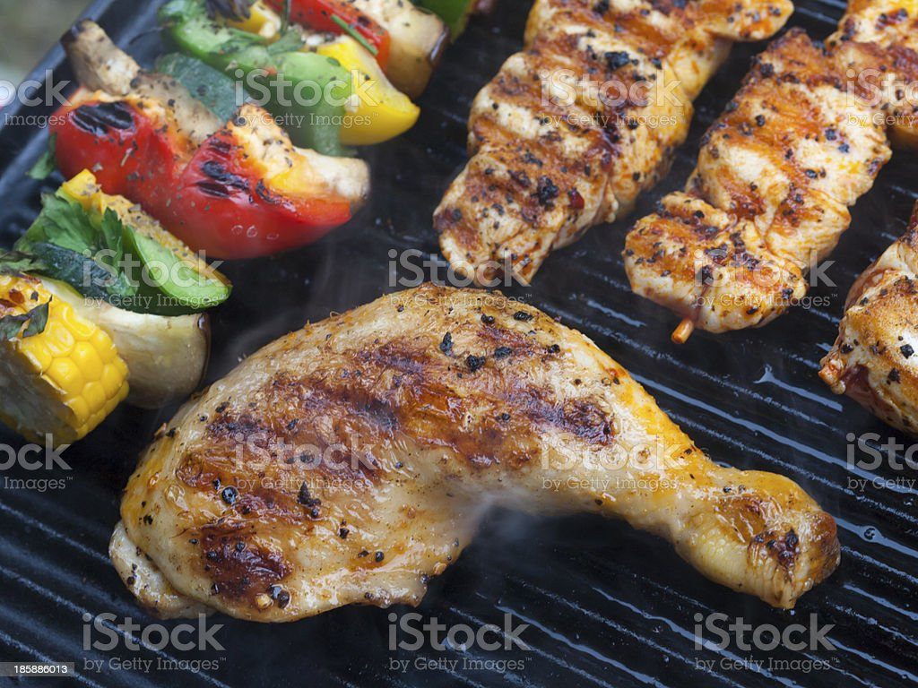 Delicious BBQ chicken meat and vegetables on a barbecue stock photo