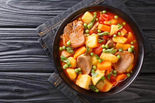 Delicious beef tongue stew with seasonal vegetables in tomato sauce close-up in a bowl. horizontal top view stock photo