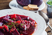 Vegetable soup - red borsch  in a white bowl on a rustic wooden background, clouse up. Healthy beetroot soup, vegetarian food. Delicious beet soup with croutons.
