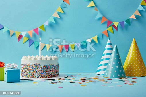 istock Delicious birthday cake, gifts, party hats and confetti on blue background with bunting 1070141686