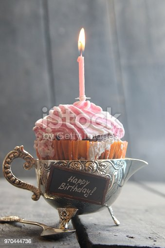 birthday cupcake with single candle, on vintage wooden table