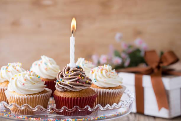 Cupcakes deliciosos de aniversário com uma vela - foto de acervo