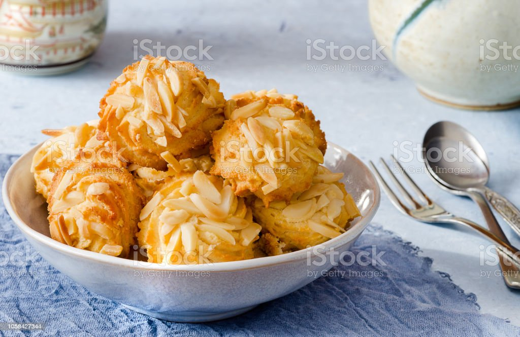 Delicious biscuits with almonds on delicate blue background - foto stock