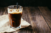 Black iced coffee in a tall glass with a straw on a rustic wooden table