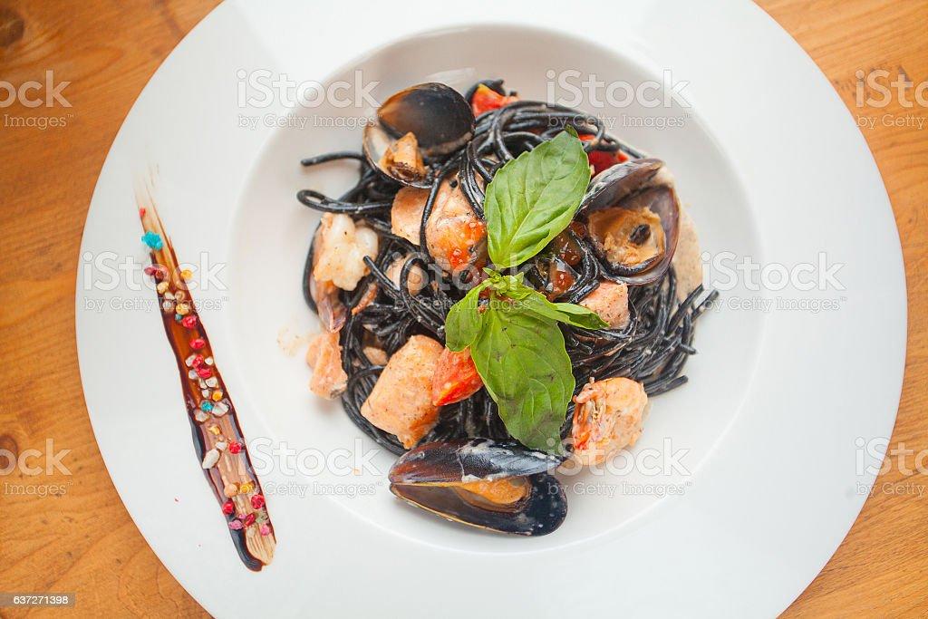 delicious black spaghetti Neri with cream sauce and seafood stock photo