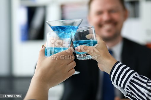 Focus on people hands holding colorful drinks in glasses. Friendly team celebrating signing of good deal or contract. Teamwork concept. Blurred background