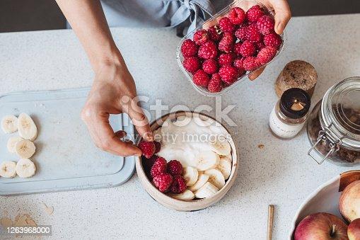 Healthy breakfast: anonymous woman making oatmeal with Greek yoghurt, raspberries, strawberries and a banana, a close up.