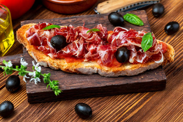 Delicious bread toast with natural tomato, extra virgin olive oil, Iberian ham, black olives and basil leaves. On wooden background. Delicious bread toast with natural tomato, extra virgin olive oil, Iberian ham, black olives and basil leaves. On wooden background. iberian stock pictures, royalty-free photos & images