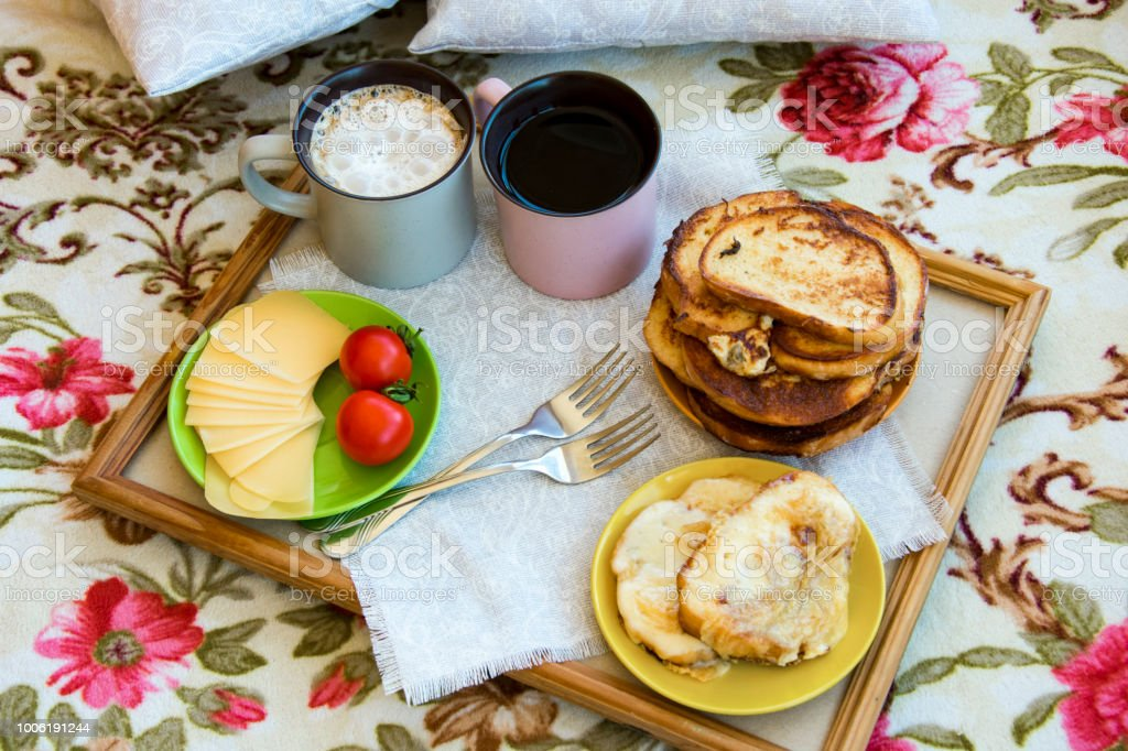 Delicious breakfast in bed with toast and a big cup of coffee