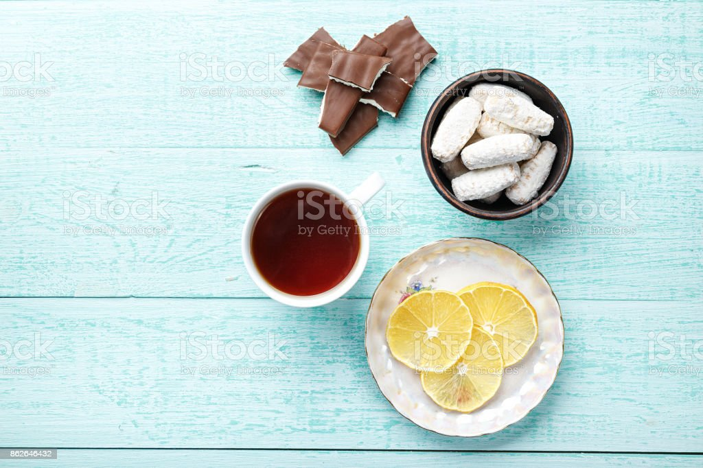 delicious breakfast of tea with lemon and biscuits on a wooden background stock photo