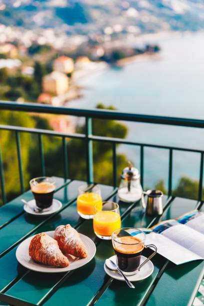 Delicious breakfast with coffee, pastry, and orange juice served on the balcony with sea view. stock photo