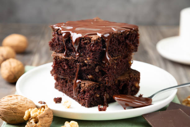 Delicious brownies with melted chocolate on a stack Chocolate spongy brownie cakes with walnuts and melted chocolate topping on a stack cake stock pictures, royalty-free photos & images