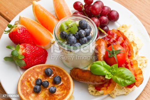 Delicious brunch with yogurt, eggs, bacon, sausages, pancaces and fresh fruit and vegetables