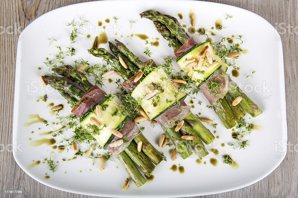 Delicious bunch of asparagus rolled with ham, zucchini, pine nut royalty-free stock photo