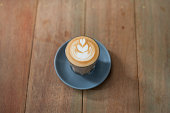 Delicious caffe latte with foam art on top of wooden table