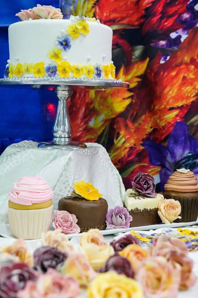 leckeren kuchen und cupcakes mit essbaren blüten - vegane hochzeitstorte stock-fotos und bilder