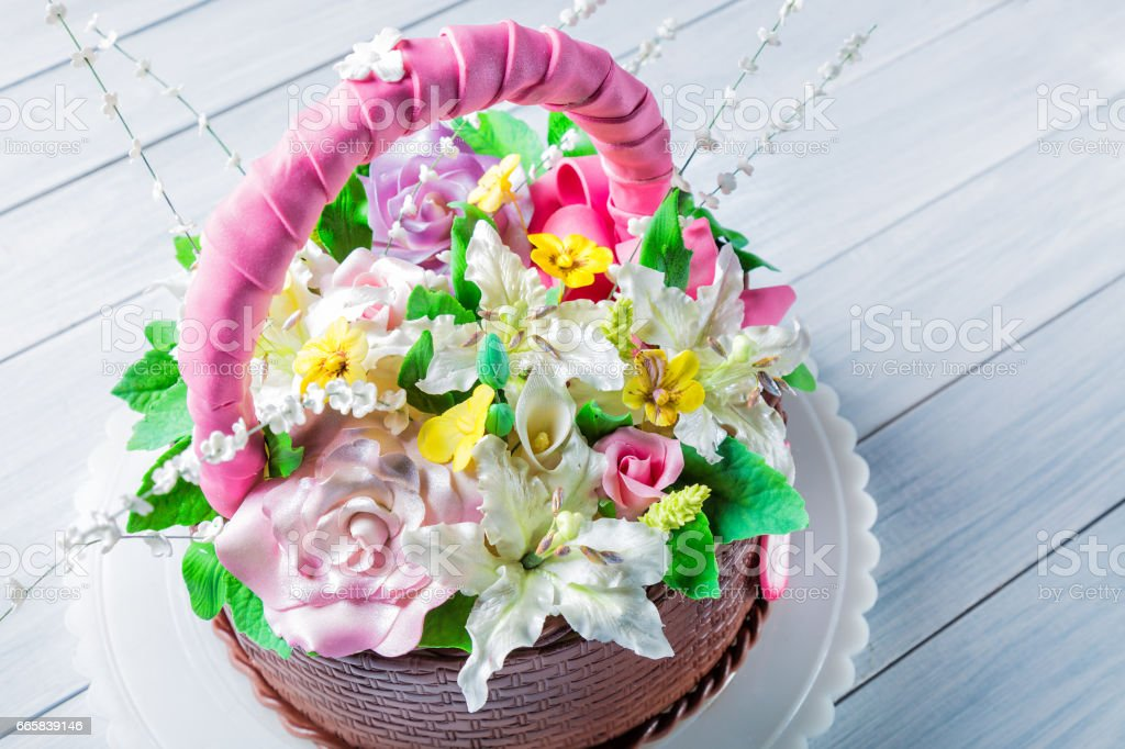 Delicious Cake Basket With Various Flowers On White Wooden Table