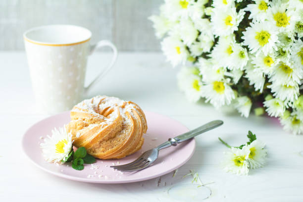 Delicious cake with coconut chips on pink plate on white table, autumn white chrysanthemum and cup of coffee stock photo