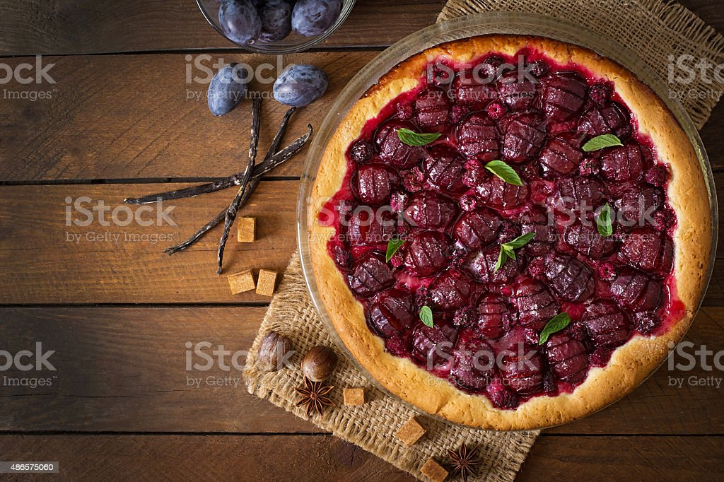 Delicious cake with fresh plums and raspberries stock photo