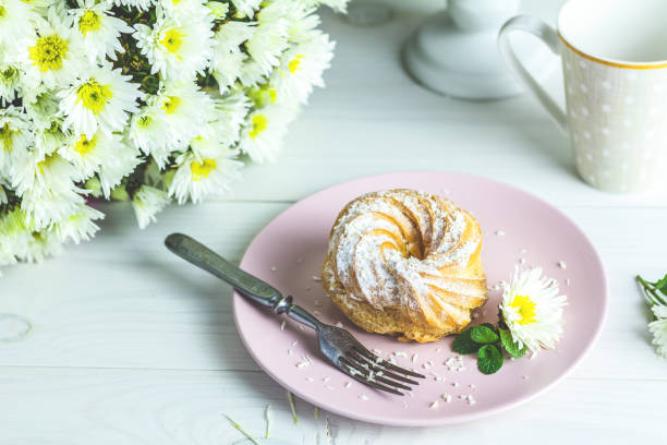 Delicious cakes with coconut chips on pink plate on white table stock photo