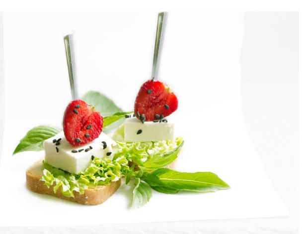 美味的小吃 wiyh 羊乳酪, 草莓黑芝麻和新鮮的羅勒葉子在白色分離 - 開胃菜 個照片及圖片檔