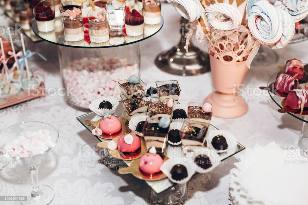 delicious candy bar at luxury  wedding reception. exclusive expensive catering. table with modern desserts, cupcakes, sweets with fruits. space for text. baby or bridal shower. holiday celebration stock photo