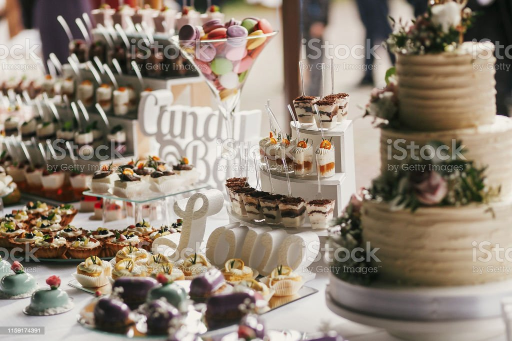 Delicious Candy Bar At Wedding Reception White And Chocolate Desserts With Fruits Macarons Cake Cupcakes On Stand Modern Sweet Table At Wedding Or Baby Shower Luxury Catering Concept Stock Photo Download