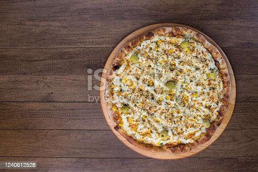 Delicious Catupiry Chicken flavored Pizza served on a wooden board. Made with Mozzarella, Chicken, Creamy Curd, Green Olives, Corn and Red Tomato Sauce.Top photograph Horizontal.