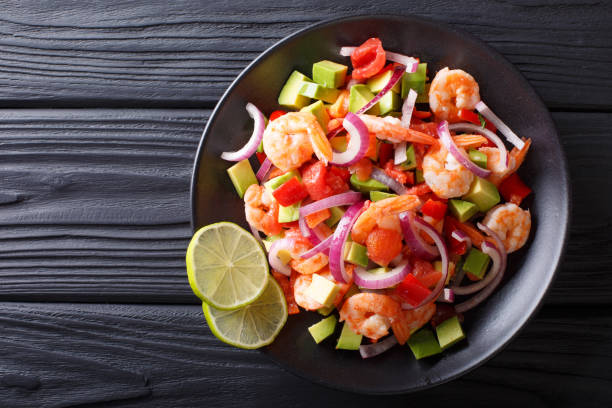 Delicious ceviche of shrimp with vegetables, spices and lime close up on a plate. horizontal top view Delicious ceviche of shrimp with vegetables, spices and lime close up on a plate on the table. horizontal top view from above peruvian culture stock pictures, royalty-free photos & images