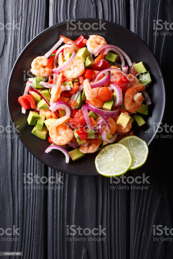 Delicious ceviche of shrimp with vegetables, spices and lime close up on a plate. Vertical top view stock photo