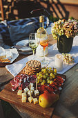 istock delicious cheese, ham and fruits served on wooden cutting board outdoor on summer garden party 1125372820