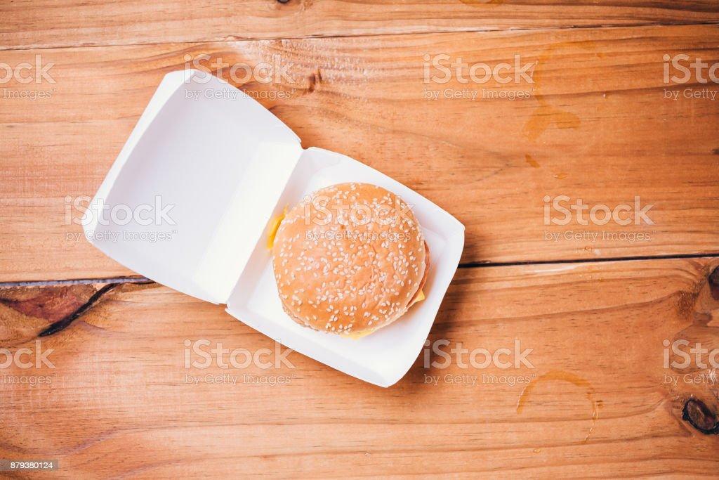 Cheeseburger délicieux dans une boîte en carton sur fond en bois - Photo