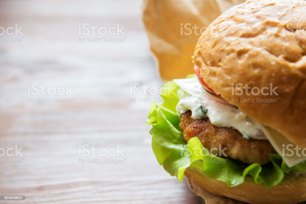 Delicious cheeseburger stacked high with a juicy beef patty, cheese, fresh lettuce, onion and tomato on a fresh bun with sesame seed standing on brown paper on a wooden tabletop with copyspace stock photo