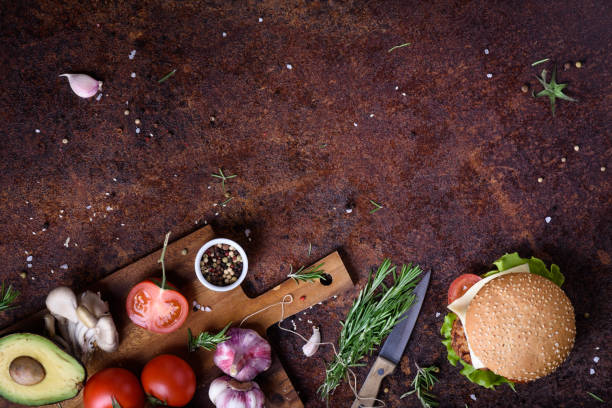 Delicious cheeseburger with a  beef patty, cheese, fresh lettuce, mushrooms and tomato on a fresh bun with sesame seed on a rustic tabletop. stock photo