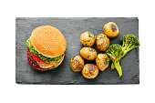 istock Delicious cheeseburger with baked potatoes 1165132910