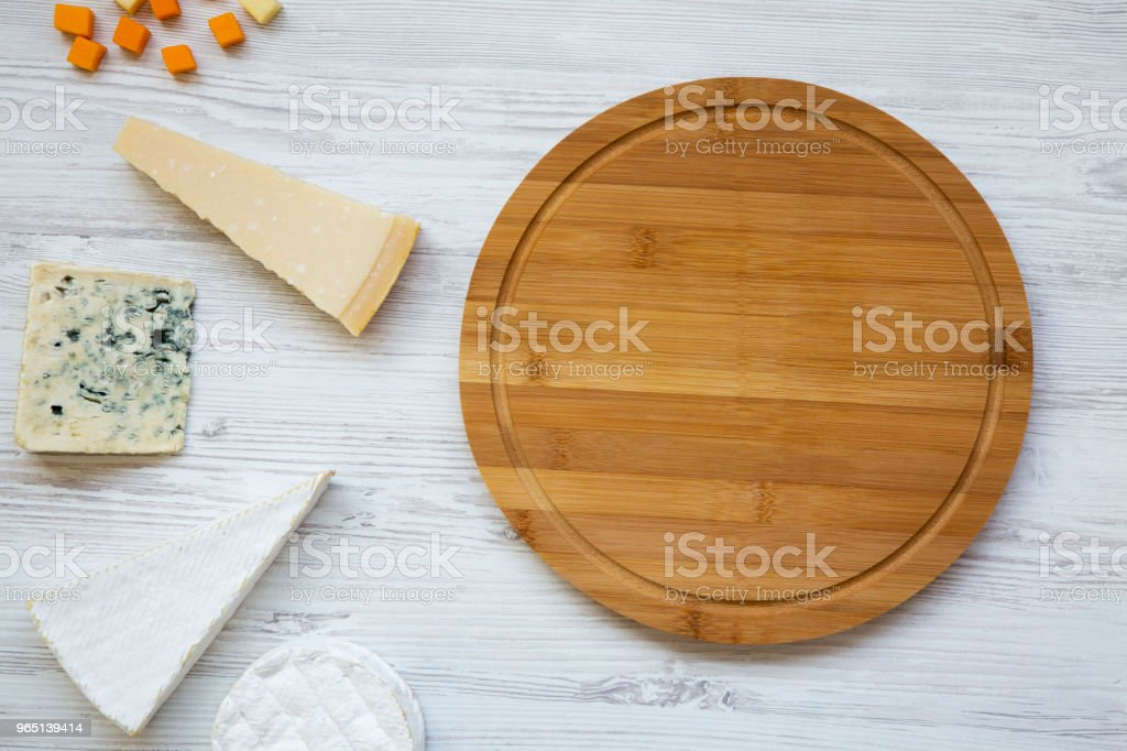 Delicious cheeses with round bamboo board on a white wooden background, top view. From above, flat lay. zbiór zdjęć royalty-free