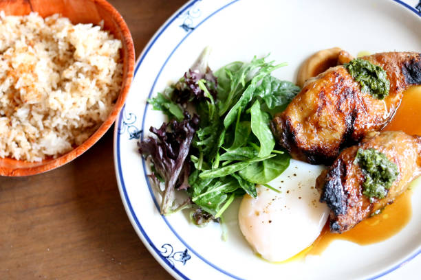 Delicious chicken adobo brunch fusion, with poached egg and salad stock photo