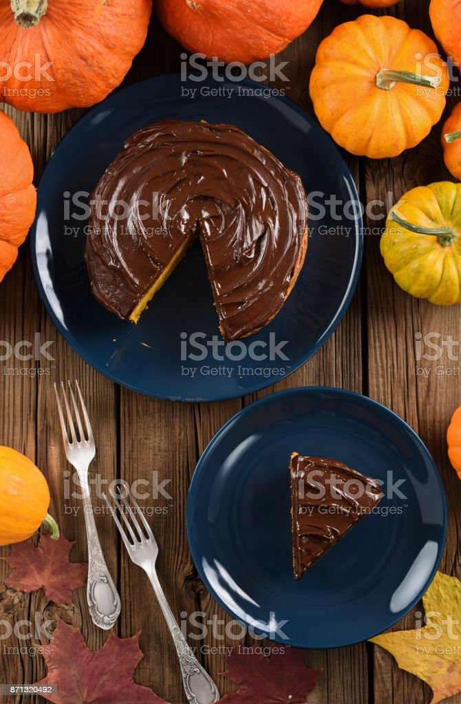 Delicious chocolate cake served on dark blue plates with bright orange pumpkins and marple leaves stock photo
