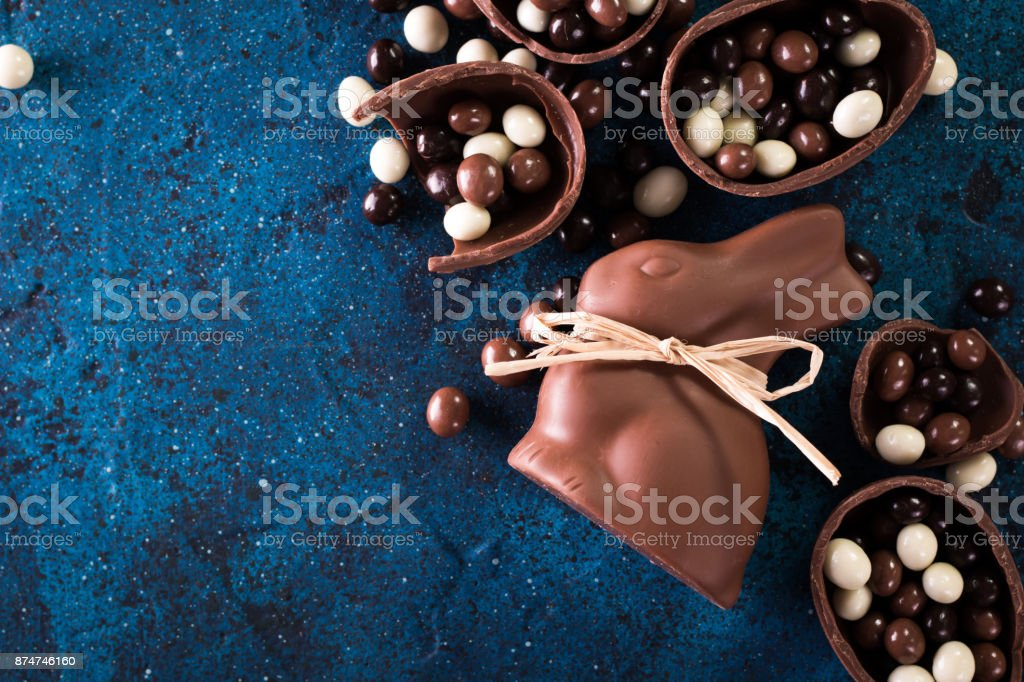 Delicious chocolate easter eggs ,bunny and sweets on dark blue background stock photo