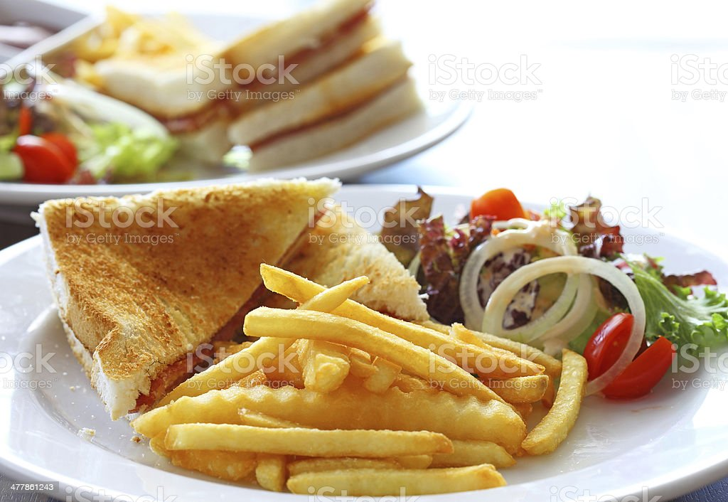 Delicious club sandwich with french fries and salad royalty-free stock photo