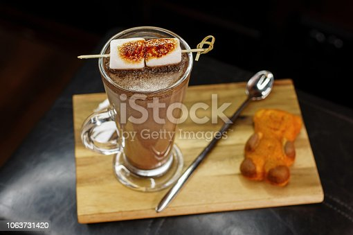 istock Delicious coffee cocktail with marshmallows with teddy bear cookies on a wooden board 1063731420