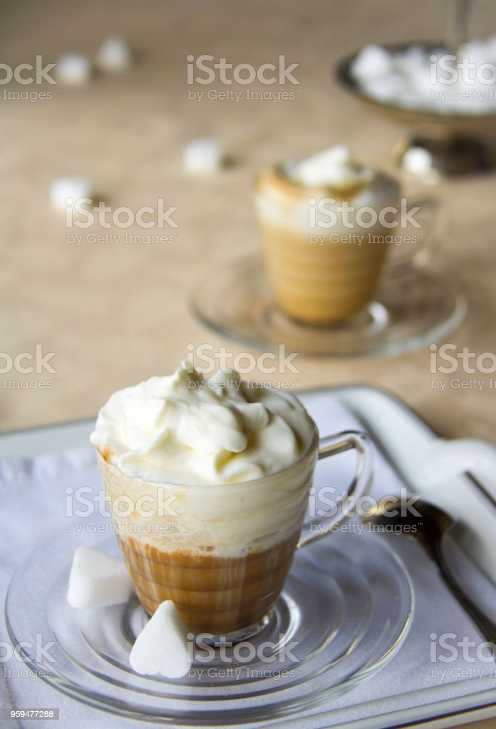 delicious coffee cups with cream on a yellow table cloth, selective...
