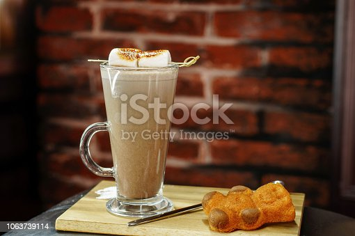 istock Delicious coffee with marshmallows and sweet bear cookies on a wooden board 1063739114