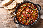 Delicious cowboy stew of beans with ground beef, bacon in a spicy sauce closeup in a bowl on the table. Horizontal top view from above