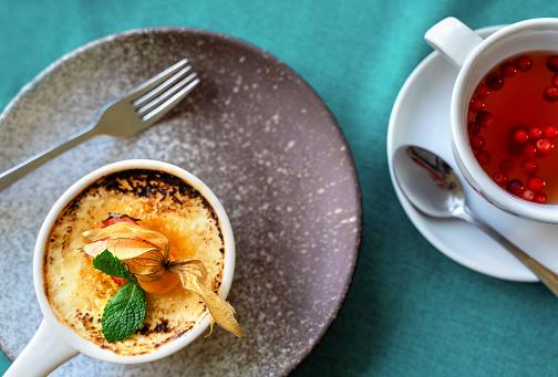 Cream brulee served in white ramekin and espresso coffee.