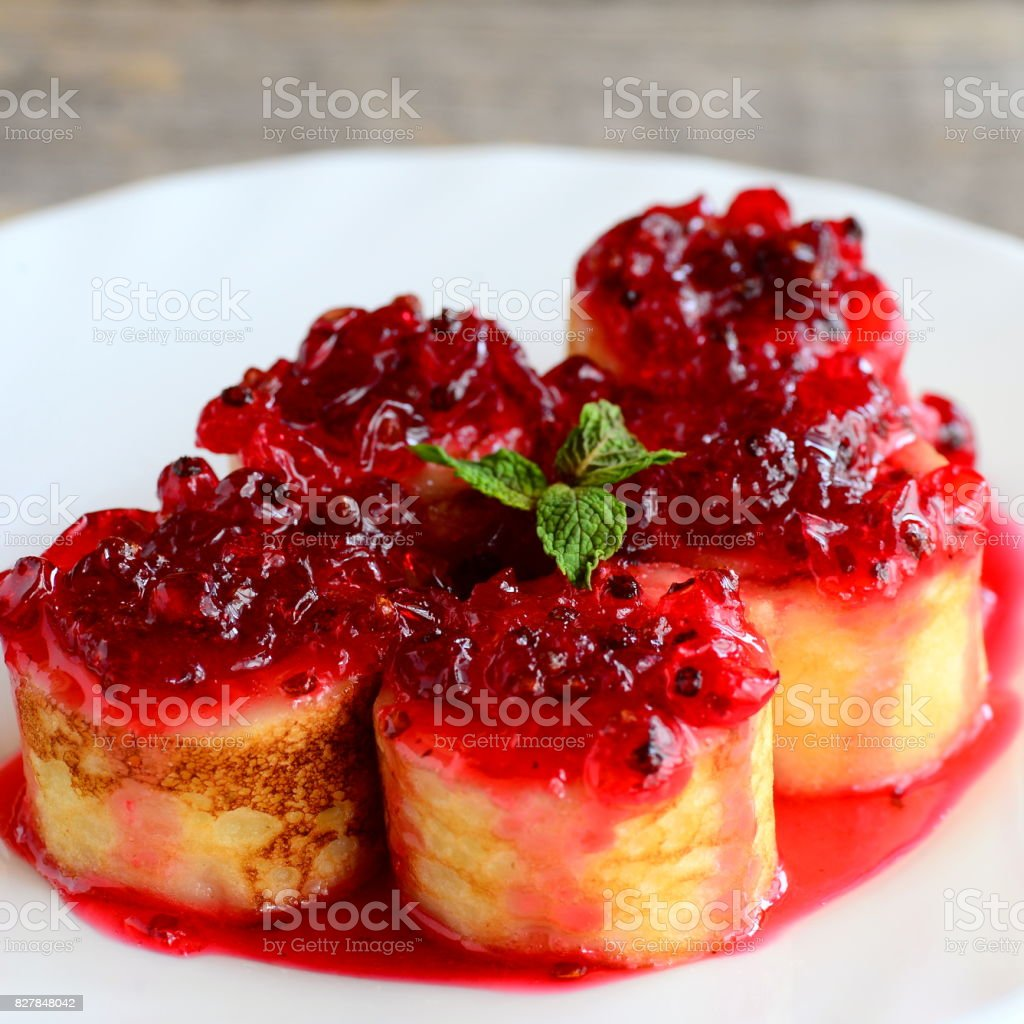 Delicious crepes rolls with red currant sauce on a white plate. Fried crepes rolls recipe. Yummy Easter breakfast idea stock photo