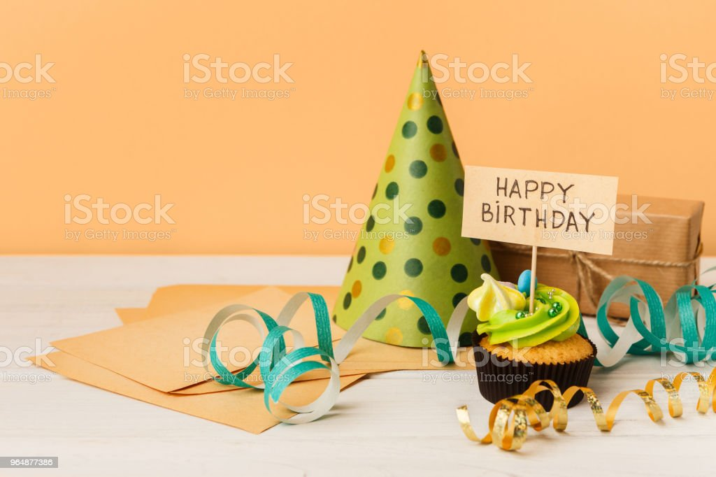 Delicious cupcake and gift on yellow background royalty-free stock photo