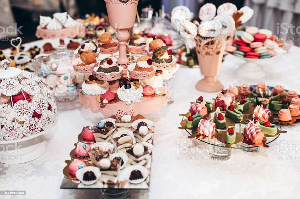 delicious cupcake. candy bar at luxury wedding reception. exclusive expensive catering. table with modern desserts, cupcakes, sweets with fruits. space for text. baby or bridal shower. stock photo