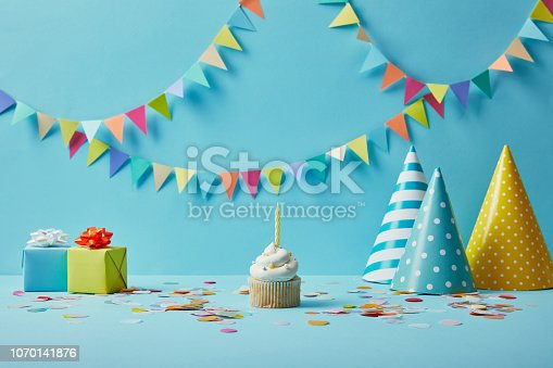 istock Delicious cupcake, party hats, confetti and gifts on blue background with colorful bunting 1070141876